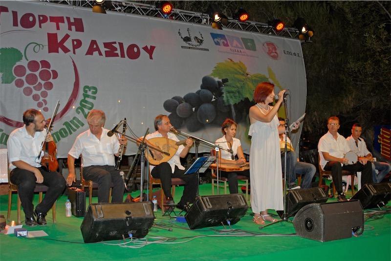 Γιορτή Κρασιού 2013, παρουσιάζει η γ.γ. της Ε.ΠΟ.Φ.Ε. κ. Γεωργία Αγγελινά (5/8/2013, προφίλ Facebook κ. Αγγελινά)