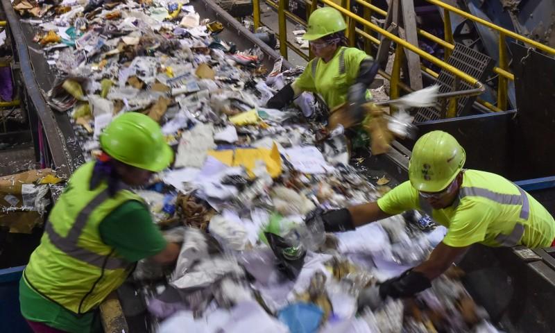 Οι εργαζόμενοι ταξινομούν απορρίματα στο εργοστάσιο ανακύκλωσης υλικών της Waste Management στο Elkridge. Η ζήτηση για ανακυκλωμένο χαρτί και χαρτόνι παραμένει κοντά στα χαμηλά δεκαετίας (Φωτογραφία: Ricky Carioti/Washington Post)